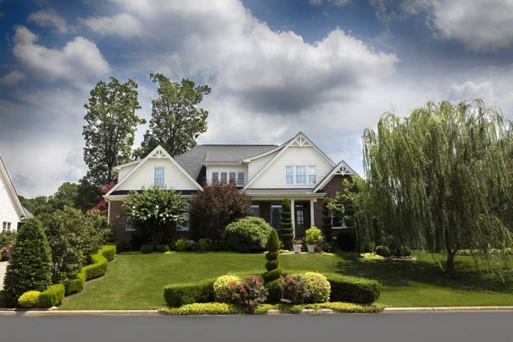 Home with lawn maintained and beautiful landscaping.
